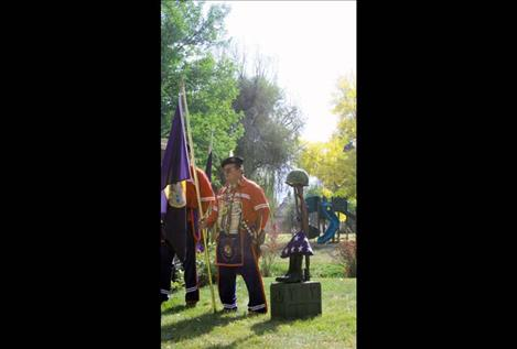 Veteran Warrior Society member Bill Rogers holds the Montana state flag during the ceremony.