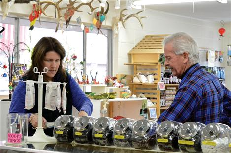 Shop owner Tony Hoyt helps customer Lori McCarthy make her selections