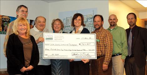 Members of Lake County Community Development Corporation accept USDA funding Nov. 19 from Anthony J. Preite, Montana state director, USDA Rural Development. Pictured above, from left, are Carol Cunningham, client services manager; Steve Dagger, LCCDC board vice president; Anthony J. Preite; Billie Lee, director of special programs; Gypsy Ray, executive director; John Winegart, loan portfolio manager; Brennin Grainey, board president; Paul Soukup, board secretary and treasurer.