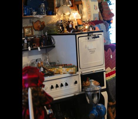 A vintage enamel stove, in  good condition, displays lots of vintage items, such as lamps, pie plates and crockery.