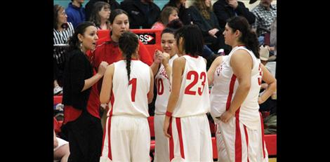 Lady Eagle Coach Erica Shelby offers fist bumping encouragment to her team between quarters.