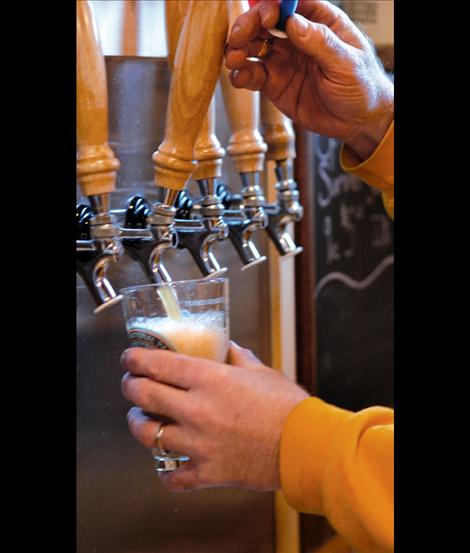 """Dave Ayers pours Glacier Brewery beer from the tap. """"Here it is — love in a glass,"""" Ayers said."""