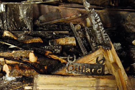 A metal sign with Val's last name is found in the charred remains of the home