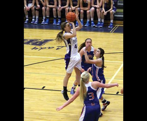 MaKenna Weltz jumps above opponents reach to make shot in Saturday's game against Columbia Falls.