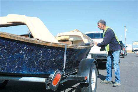 Johnny Eggebrecht inspects a boat at the Ronan checkpoint on U.S. Highway 93 before it heads to Flathead Lake.