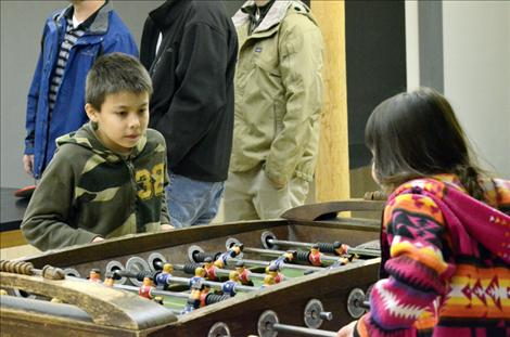Isaac Gloover, 9, and Alexis Gloover, 7, try out the foosball table in the waiting area at the Cross Collar Academy.
