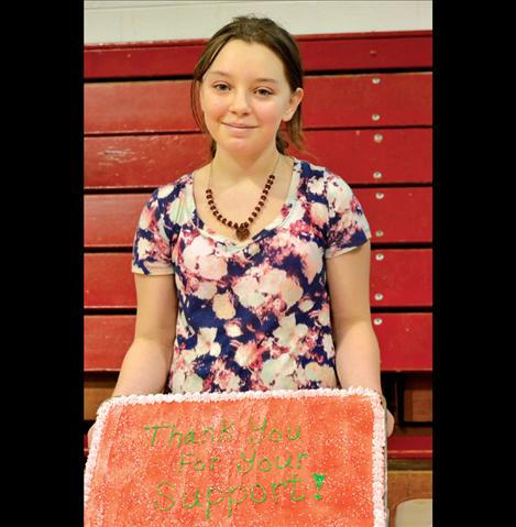 Keisha Dillard, 12, holds up a cake before it was sliced during the fundraiser for her family, who lost everything when their home burned to the ground in December.
