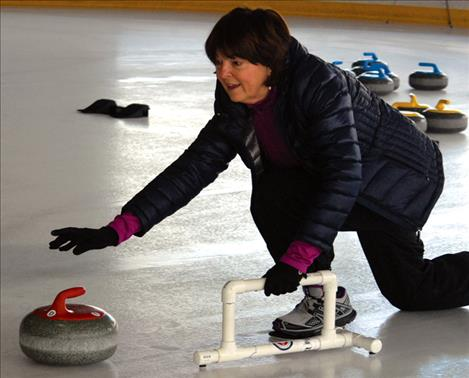 Connie Brownell releases her stone,  using a stabilizer  to hold the  classic curler's  push-off.