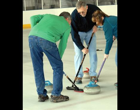 Curlers Gayle Seimers, left, Allen Bone and Wendy Scheffler sweep to keep the stone sliding.