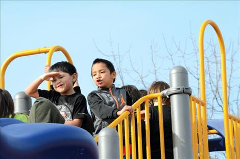 Children grin from ear to ear while playing on new equipment in St. Ignatius.