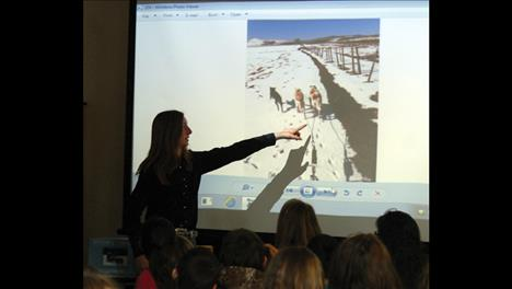 Charmayne Morrison points to a video of her dogs running in the snow this winter as she explains the sport to Polson Middle School kids.