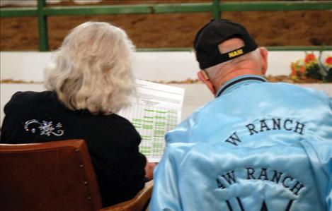 Jean and Bob Harshberger check the Valley View Charolais Ranch bull sale catalog as they bid on bulls at the sale.