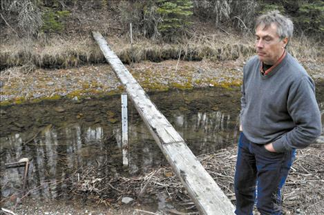 Tribal hydrologist Seth Makepeace stands near part of a water measurement system in Pablo