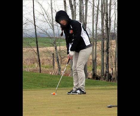 Bundled up to fight the chilly spring weather freshman Brooklyn Olson putts on the soggy green. Olson placed first at Ronan's home tournament and then went on to place fourth in Plains on Saturday.