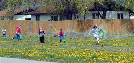 Looking to fill up their bags with trash, young volunteeers scan a vacant field during Polson's 'Clean Up Green Up' event last weekend.