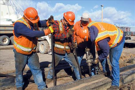 Members of the Lake County Roads Department bridge crew and the Montana Department of Transportation level and secure new rail supports before paving the road.