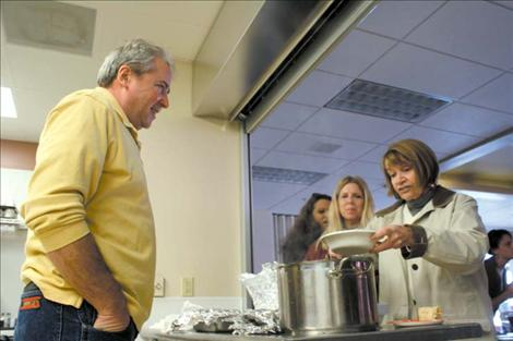 Virgil Dupuis mans the chow line as SKC's Interim Academic Vice President Alice Oechsli helps herself to some stew.