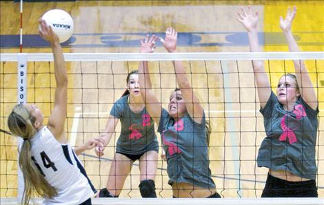 Sporting pink ribbons on their shirts in support of breast cancer  awareness, Lady Pirates Shalaina Duford and Heidi Rausch defend the net against Frenchtown, while teammate Katie Sprague provides backup. Polson won the match in a rousing victory on senior night last Thursday.
