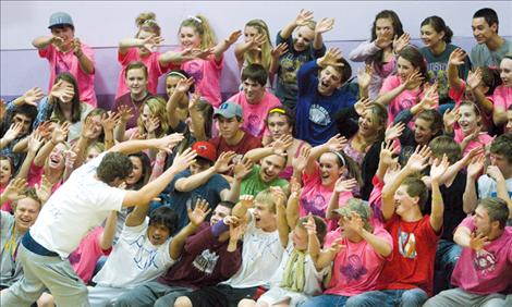 """Fans sporting pink in honor of breast cancer awareness get fired up at Polson's """"pink-out"""" volleyball game."""