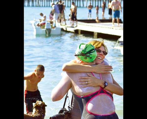 Sarah Thomas gets a hug from swimming friend Dana Johnston at Riverside Park in Polson after completing her 28-mile swim.