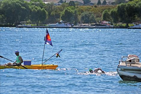 Open-water swimmer Sarah Thomas nears Riverside Park in Polson Friday, completing a 13-hour swim.