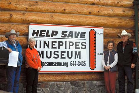 From left to right: Rod Wamsley, Laurel Cheff, Hope Stockstad and Bud Cheff pose outside the museum. Wamsley is holding the deed to the building.