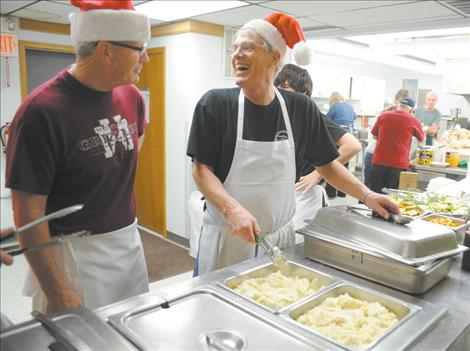 Burt Cannon, center,  demonstrates how to scoop mashed potatoes on the serving line for the Christmas dinner at the Ronan Community Center.