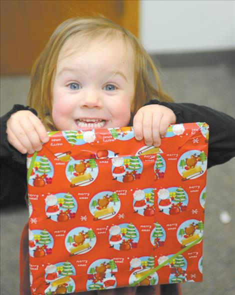 Kila Cannon  excitedly displays a gift  Santa gave her during a  community Christmas dinner held Dec. 25 at the  Ronan Community Center.