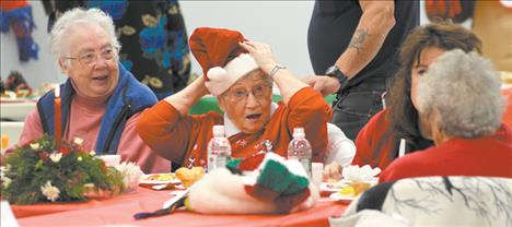 "Jim Blow/Valley Journal Marie Cowen adjusts her festive cap before sitting down for her meal at the Traditional Christmas Day Dinner held at the Ronan Community Center on Christmas Day. Cowen had so much catching up to do with friends that her dinner began to get cold. ""That's fine. Cold dinner doesn't bother me,"" the former cafe owner smiled. ""I actually digest it better when it's cold."""