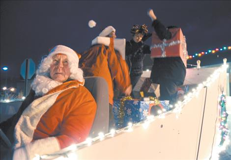 """Jack Collins, a.k.a. Santa Claus, sits patiently behind the wheel for the parade to begin while """"O'Leary's Old Ladies"""" prepare for their gala ride down Main Street."""