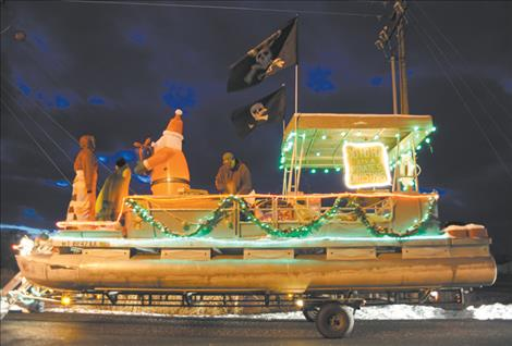 "The Fisher family puts on the finishing touches of its ""Pirates Christmas"" float as dusk wanes prior to the Ronan Parade of Lights."