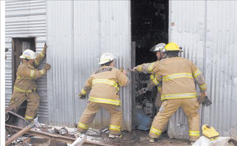 Ronan firefighters attempt to close sliding doors of the shop that caught on fire Monday afternoon. There were no injuries and minimal damage to the maintenance/junkyard shop belonging to Leroy Lake.