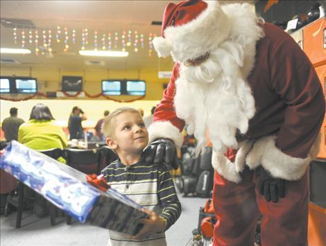 Charley Rathbun happily accepts a gift from Santa Claus, who visited him last Tuesday evening. Santa was escorted by the Ronan Fire Department aboard a fire engine. Each year, RFD firefighters donate to the Ronan Firemen's Christmas program to buy presents for local children.