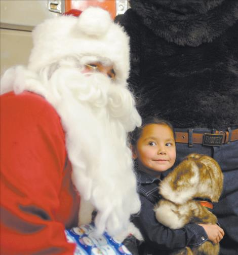 Jordan Singer shares a moment with Santa during a visit from Ronan firefighters before Christmas.