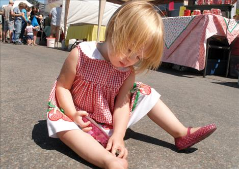 Shelly Torgenrud, age 2 of Ronan, plops down to remove her shoe, which has given her a blister. Above right, the Montecahto Club sold out of their famous cherry pies. Above right, Emma Kupper, 10, of Philadelphia, Pennsylvania, eats a red, white and blue shaved ice.