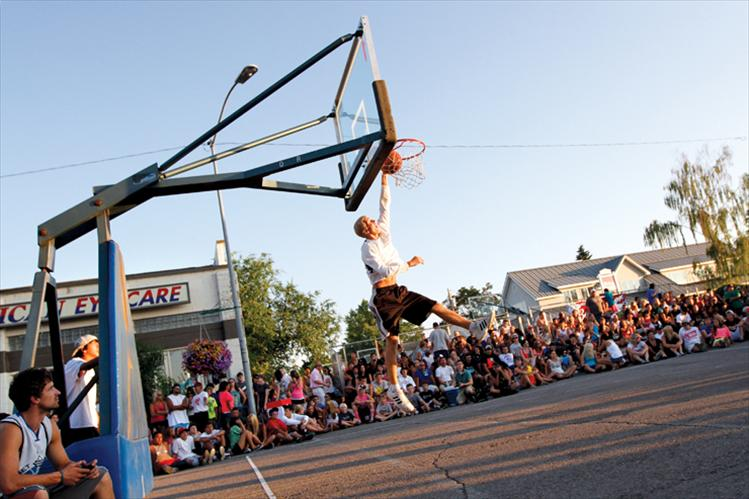 Spectators line the  sidewalks as an athlete dunks the ball while warming up for the slam dunk contest.