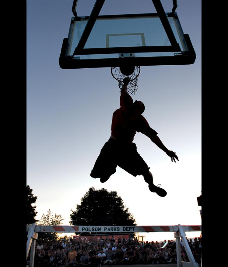 Matt Luedtke, a Ronan High School graduate, leaps over a barrier borrowed from the Polson Parks Department during the slam dunk contest at the Flathead Lake 3-on-3 basketball tournament in Polson. Luedtke's moves impressed the crowd and the judges, but he just missed his final dunk attempt to fall short of the $1,000 prize.