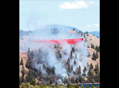 Berl Tiskus/Valley Journal A single-engine airtanker dumps fire retardant on the Wild Horse Island fire July 22.