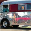 A shiny bus reflects images of visitors to last year's car show