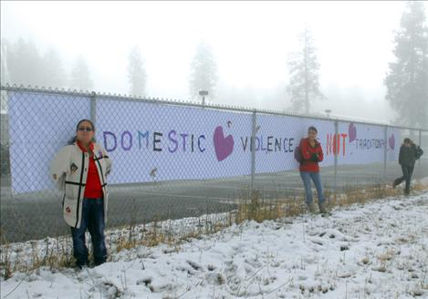 "Evelyn Hernandez, left, Ashley Lozeau and Ida Couture stand by a banner constructed by Ashley and Ida. The message reads ""domestic violence is not traditional."""