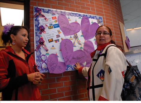 Ashley Lozeau and Evelyn Hernandez pose next to a bulletin board created in memory of women who lost their lives to domestic violence.