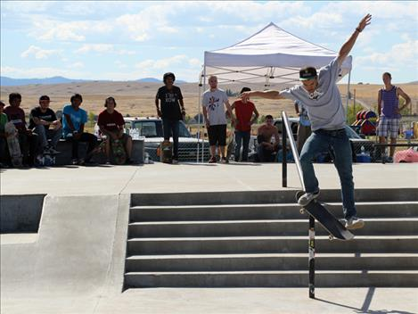 Contestants watch Skate Jam organizer Jesse Vargas slide down a rail at Saturday's event. Vargas placed first in the Rail competition.