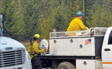 Ronan Volunteer  firefighters clean up  after dousing flames Thursday in a heavily wooded residential area in Pablo.