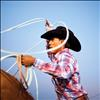A Flathead River Tour Rodeo  cowboy twirls his rope as he warms up for the compeition.