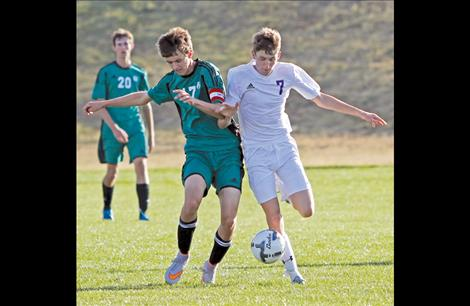 Mike Mercer tangles with a Belgrade player during Friday's game in Polson. Mercer scored the Pirates' only goal off of a penalty kick in the second half.