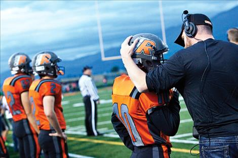 Ronan football coach Jim Benn, right, talks to Collin McGuyer during a game.