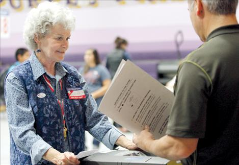 Election official Jackie Ladner helps a voter scan his ballot at Polson's Linderman gym on Election Day.