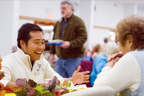 Ronald Legislador, a volunteer at last year's community Thanksgiving dinner, chats with another volunteer during a break from kitchen duty.