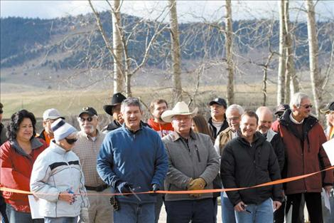 Construction workers, Tribal Council members, engineers from the CSKT, DJ&A and the county, local residents and county commissioners smile moments before the ribbon- cutting.