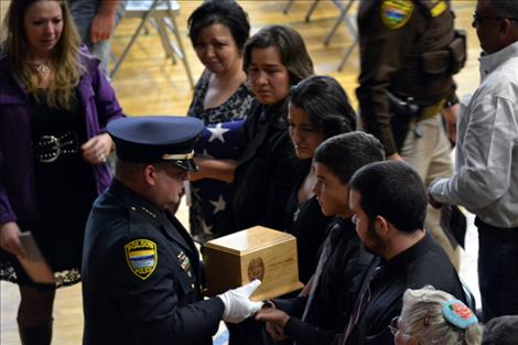 Polson Police Chief Wade Nash presents Cleveland's ashes to his family.